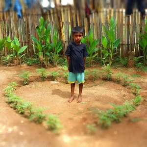 "A Tamil child poses inside a heart formed by bright green ""weeds""."